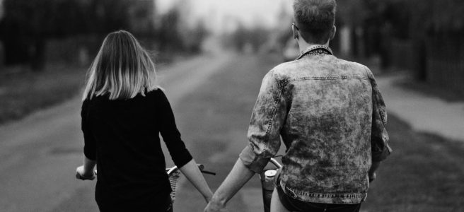 A boy and a girl bicycle up the road while holding hands.
