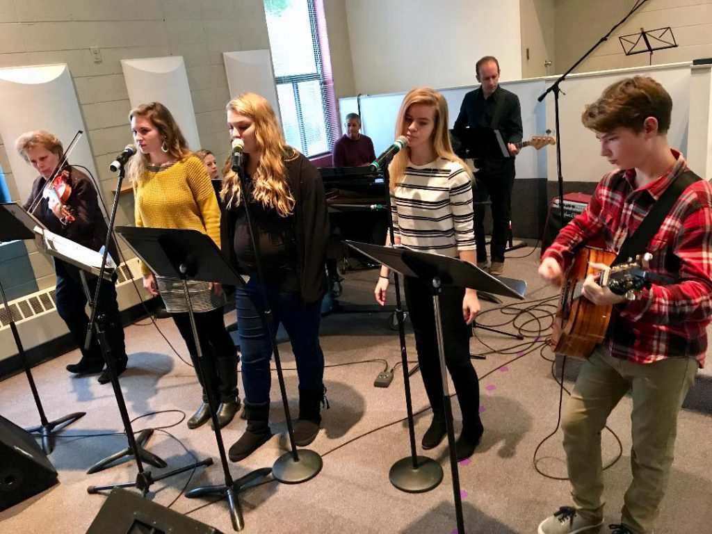 Four teenagers leading worship, plus some adult musicians backing them up.