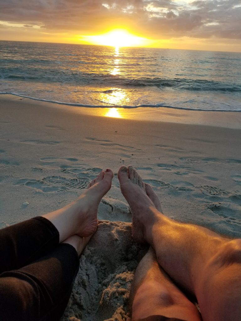 And image of a man and a woman's crossed bare feet on the beach at sunset.